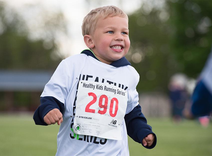 little boy smiles during run