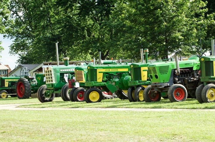 Fronts of Green Tractors on Display in a Rural Field
